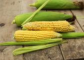 čerstvé kukuřice na dřevěné pozadí — Stock fotografie