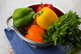 Fresh peppers in bowl on white table — Stock Photo