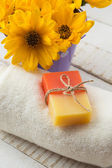 Natural handmade soap on towel and flowers — Stock Photo