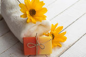 Bar of natural handmade soap, towel and flowers — Stock Photo