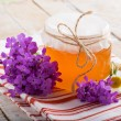 Fresh honey with flowers — Stock Photo