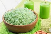 Sea salt in bowl on green towel — Stock Photo