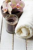 Spa concept. Bath towel, fresh flowers on white wooden backgroun — Stock fotografie