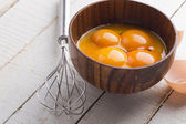 Chicken eggs in bowl on wooden background — Stock Photo