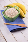 Oat flakes in bowl with bananas — Stockfoto