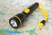 Flashlight lying on a district map — Stock Photo