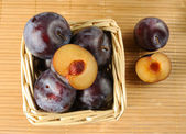 Plums in a small basket — Stock Photo