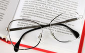 Eyeglasses lies on a open book — Stockfoto