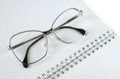 Eyeglasses lies on a notebook — Stok fotoğraf