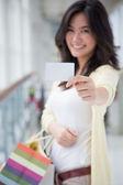 Shopaholic woman showing card — Stockfoto