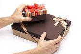 Elinde beyaz zemin üzerine hediye kutuları. — Stok fotoğraf