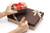Gift boxes and hand with a finger up. — Stock Photo