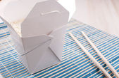 Rice in paper box with chopsticks — Stock Photo
