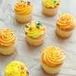 Yellow and orange cupcakes with sprinkles top view - Stock Photo