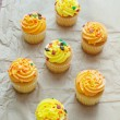 Cupcakes top view with orange and yellow frosting - Stock Photo