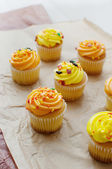 Yellow and orange cupcakes with icing — Stock Photo