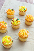 Yellow and orange cupcakes with sprinkles top view — Stock Photo
