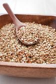 Raw buckwheat in wooden bowl closeup — Stock Photo