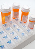 Containers with pills and weekly organizer — Stock Photo
