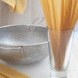 Dry spaghetti and lasagna and colander - Stock Photo