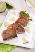 Breaded fried white fish with lime — Stock Photo