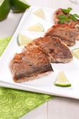 Pieces of fried fish on the square plate — Stock Photo