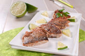 Crispy fried white fish fillets with lime — Stock Photo