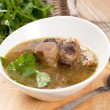 Soup with meat and bone and parsley — Stock Photo #23336984