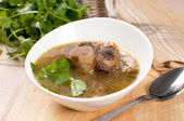 Soup with meat and bone and parsley — Stock Photo