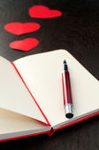 Notebook with red pen and hearts — Stock Photo