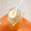 Spoon with honey above glass jar — Stock Photo
