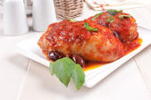 Chicken thighs sauteed with tomato and olives — Stock Photo