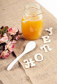 Honey jar with sign from wooden letters — Stock Photo