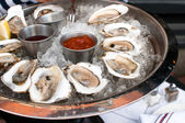 Oysters served raw with sauces — Stock Photo