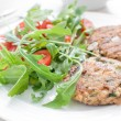 Ground fish patty with arugultomato salad — Stock Photo #29174073