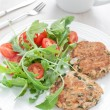 Fish patties with parsley and arugultomato salad — Stock Photo #29174135