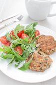 Fish patties with parsley and arugula tomato salad — Stock Photo