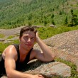 Young man relaxing on the top of the mountain — Stock Photo