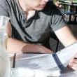 Young man in restaurant reading menu — Stock Photo