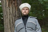Young man in a cossack clothes in a forest — Stock Photo