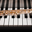 Stock Photo: 14k Rose gold flute on piano keys
