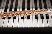 14k Rose gold flute on a piano keys — Stock Photo