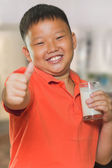 Young Asian boy with a glass of milk — Stock Photo