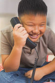 Young Asian boy looks happy on the phone — Stock Photo