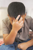 Young Asian boy looks desperatly on the phone — Stock Photo