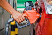 Closeup of a fueling hose at a gas station with a Hand — Stock Photo