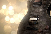 Black electric guitar over a bokeh background — Stock Photo