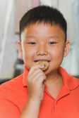 Young asian boy eats a piece of biscuit — Stock Photo