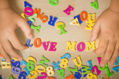 Hands of a boy putting -love mom- plastic alphabets together. — 图库照片