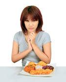 Isolado jovem mulher asiática com um donuts na mesa — Fotografia Stock